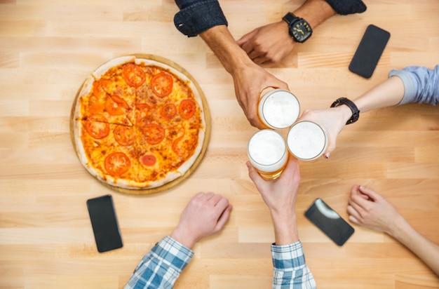 Draufsicht der multiethnischen gruppe junger leute, die bier trinken und pizza essen