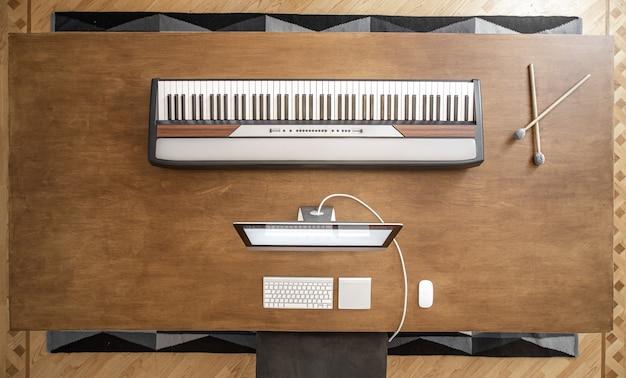 Draufsicht der musikalischen schlüssel und des computers auf einem großen holztisch. musikerarbeitsplatz, musikalischer minimalismus.