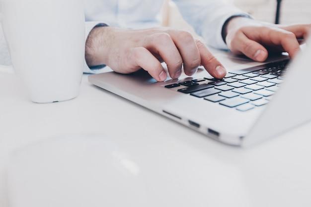 Draufsicht der nahaufnahme des mannes arbeitend an laptop