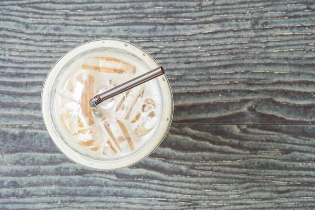 Draufsicht der nahaufnahme des plastiktasse kaffees auf unscharfem holztisch maserte hintergrund
