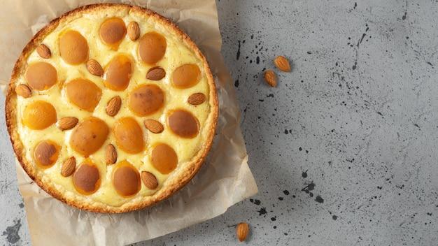 Draufsicht der nahaufnahme des selbst gemachten aprikosenkuchens mit mandeln.