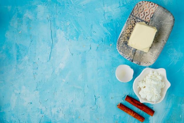 Draufsicht der nahrungsmittel als butterhüttenkäsezimt mit eierschale auf blauem hintergrund mit kopienraum