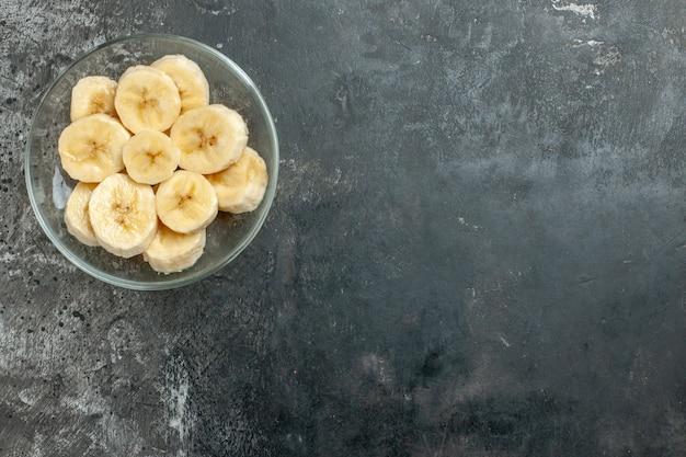 Draufsicht der nahrungsquelle frische bananen, die in einem glastopfmesser auf grauem hintergrund gehackt werden