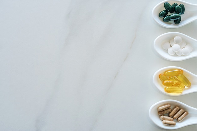 Draufsicht der natürlichen vitaminergänzung auf weißem löffel als rahmen des marmorbeschaffenheitshintergrunds. trendkonzept des gesunden essenslebensstils.