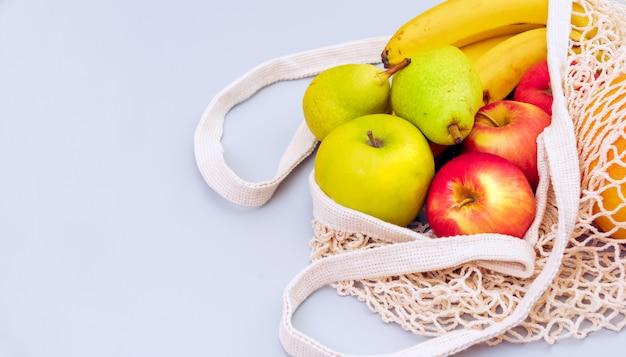 Draufsicht der netzeinkaufstasche mit organischen öko-früchten lokalisiert auf hellblauem raum.