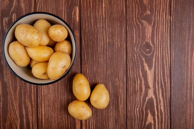 Draufsicht der neuen kartoffeln in der schüssel auf holzoberfläche mit kopienraum