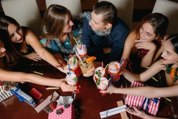 Draufsicht der neujahrsfeier. liebespaar bei weihnachtsfeier, glückliche freunde mit cocktails. clubhintergrund, romantische stimmung