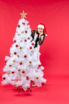 Draufsicht der neujahrsstimmung mit glücklichem schönem mädchen in einem schwarzen kleid mit weihnachtsmann-hut, der sich versteckt
