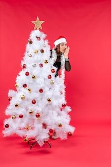 Draufsicht der neujahrsstimmung mit schönem mädchen in einem schwarzen kleid mit weihnachtsmannhut, der sich hinter weihnachtsbaum versteckt