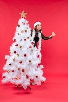 Draufsicht der neujahrsstimmung mit schönem mädchen in einem schwarzen kleid mit weihnachtsmannhut
