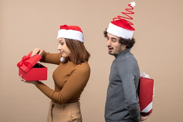 Draufsicht der neujahrsstimmung und des partykonzepts - überraschtes reizendes paar, das geschenke hält, die weihnachtsmann tragen