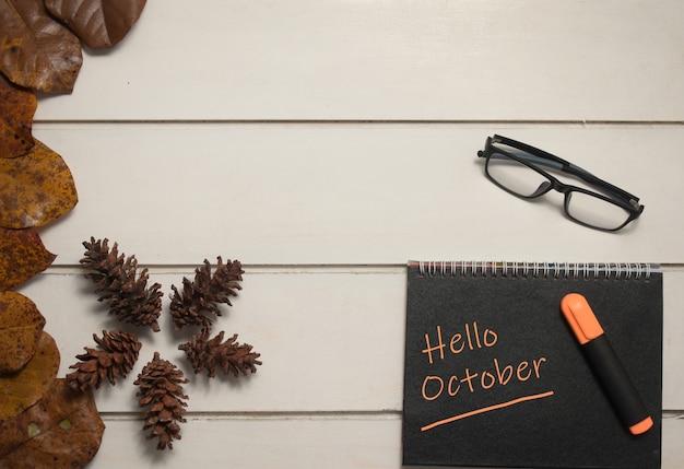Draufsicht der notiz mit worten hallo oktober und brille auf einem hölzernen hintergrund. herbstkonzept