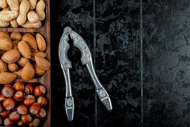 Draufsicht der nussmischung haselnüsse mandel und erdnüsse in der schale mit nussknacker auf schwarzem hintergrund mit kopienraum