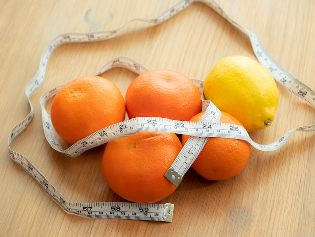 Draufsicht der orange, zitrone, messendes band veranschaulichen zum naturprodukt für gewichtsverlustdiät