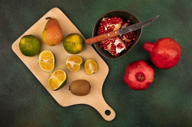 Draufsicht der organischen mandarinen auf einem hölzernen küchenbrett mit messer mit köstlichen früchten wie birnen-kiwi und granatapfel auf einer schüssel