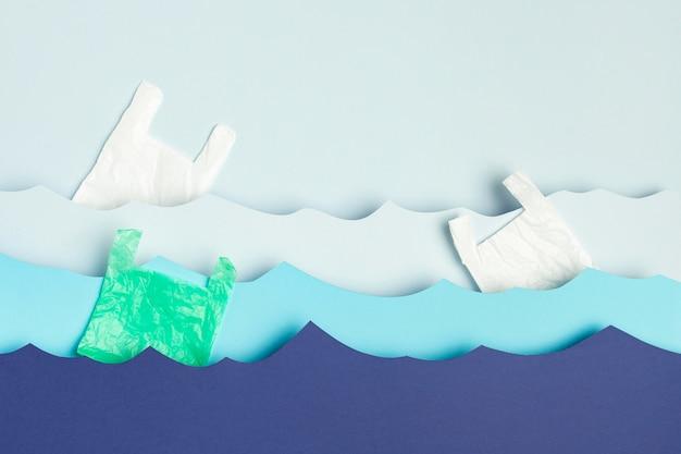 Draufsicht der papierozeanwellen mit plastiktüten