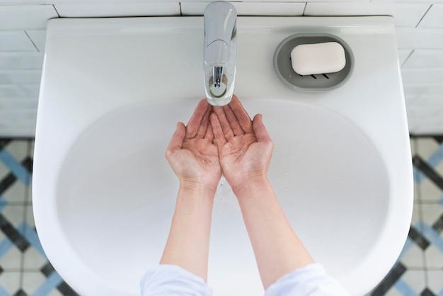 Draufsicht der person, die ihre hände am waschbecken wäscht