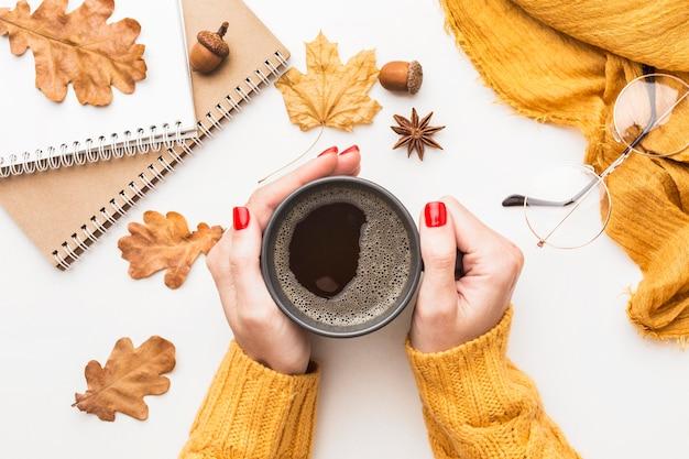 Draufsicht der person, die kaffeetasse mit herbstlaub hält