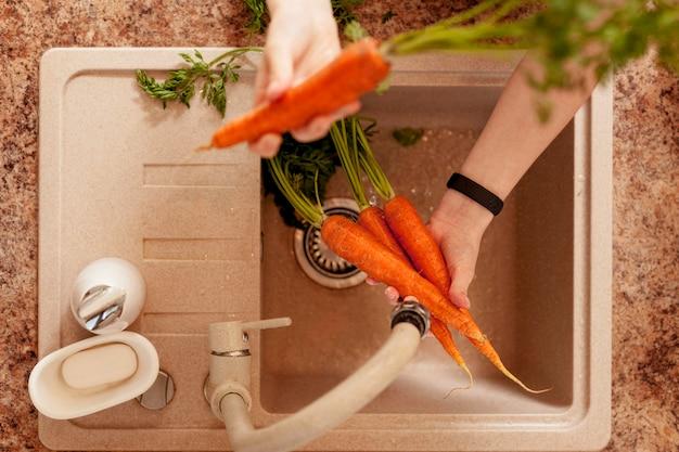 Draufsicht der person, die karotten in vorbereitung auf das abendessen wäscht