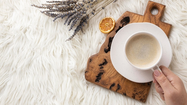 Draufsicht der person, die tasse kaffee mit lavendel und getrockneten zitrusfrüchten hält