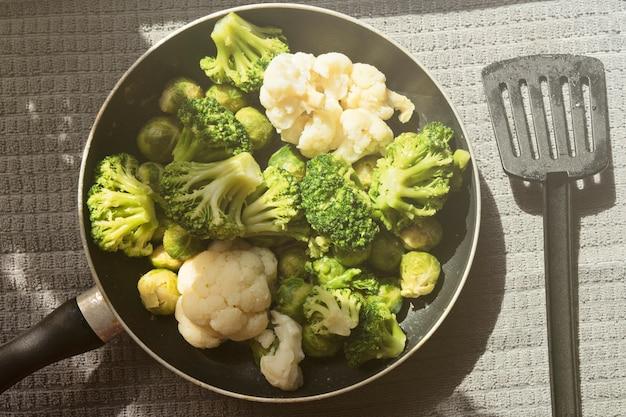Draufsicht der pfanne mit frisch aufgetautem gemüse: blumenkohl, brokkoli, rosenkohl