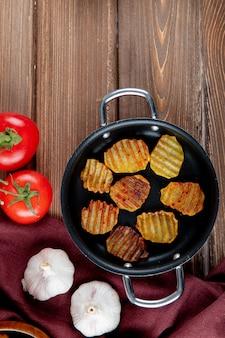 Draufsicht der pfanne mit kartoffelchips und -gemüse als knoblauch und tomate auf hölzernem hintergrund mit kopienraum