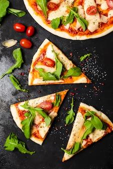 Draufsicht der pizza auf schwarzer schiefertabelle