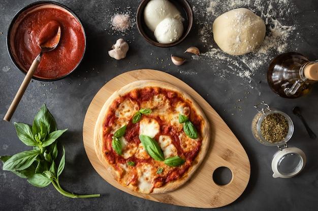 Draufsicht der pizza margherita auf dem tisch mit rohem teig