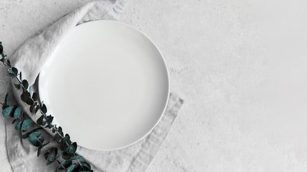 Draufsicht der platte auf stoff mit blättern und kopierraum
