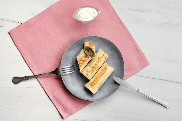 Draufsicht der platte mit dünnen pfannkuchen gefüllt mit hasenhackfleisch