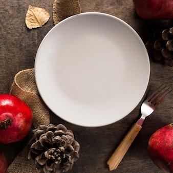 Draufsicht der platte mit herbstgranatapfel und tannenzapfen