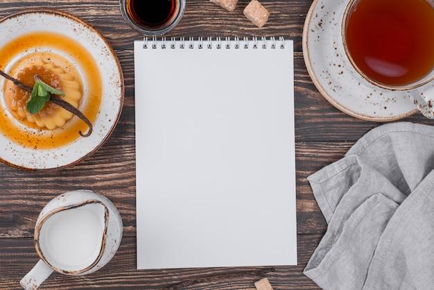 Draufsicht der platte mit vanillesoße und notizbuch