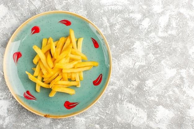 Draufsicht der pommes frites, die innerhalb der blauen platte lecker sind