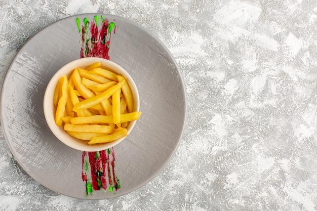 Draufsicht der pommes frites innerhalb der kleinen weißen platte auf der grauen hellen oberfläche