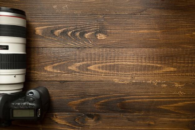Draufsicht der professionellen digitalkamera mit teleobjektiv auf holzhintergrund mit exemplar background