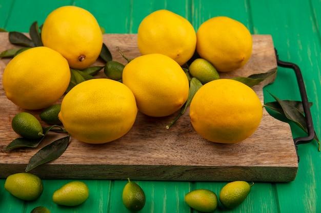 Draufsicht der reich an vitaminenfruchtzitronen mit blättern lokalisiert auf einem hölzernen küchenbrett auf einer grünen holzwand