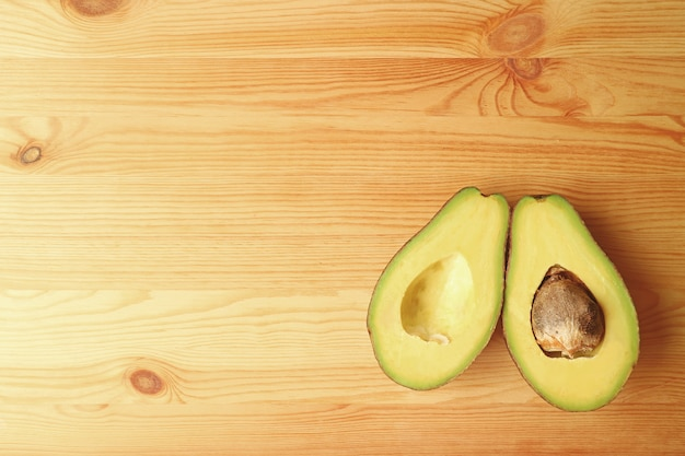 Draufsicht der reifen avocados-frucht geschnitten zur hälfte auf hölzernem hintergrund