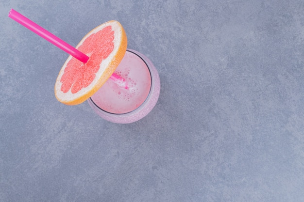 Draufsicht der reifen grapefruit mit glas saft auf grauem hintergrund.