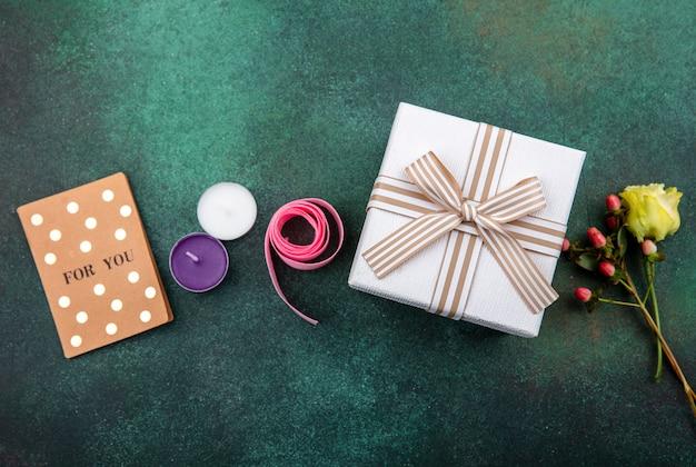 Draufsicht der reizenden und zarten blume mit geschenkbox auf grüner oberfläche