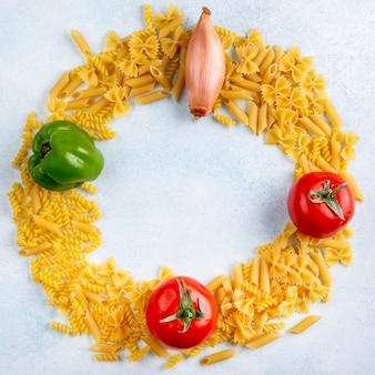 Draufsicht der rohen nudeln mit tomatenzwiebeln und paprika auf einer grauen oberfläche