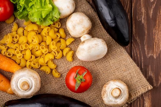 Draufsicht der rohen nudeln und des champignons der frischen pilze mit karotten-tomaten und salat auf sackleinenhintergrund