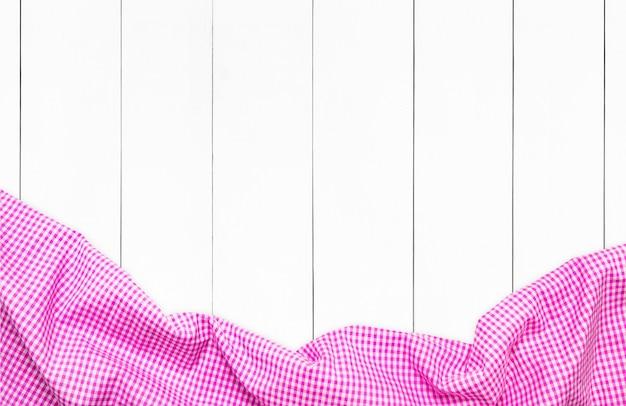 Draufsicht der rosa karierten serviette auf weißem holztischhintergrund. küchentuch