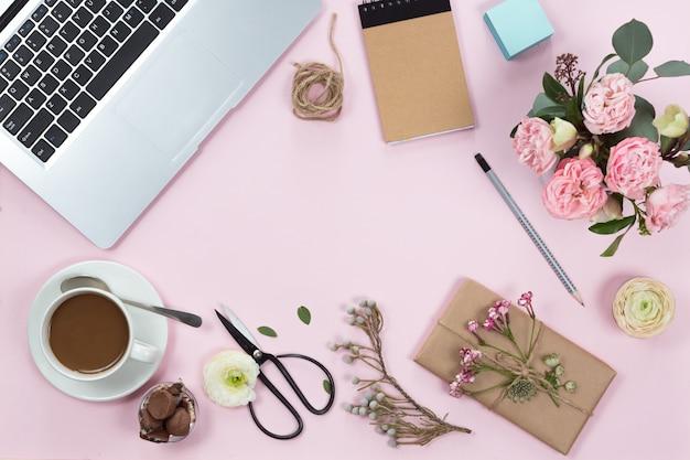 Draufsicht der rosa schreibtischtabelle mit laptop, smartphone, tasse kaffee und blumen. textfreiraum, flach zu legen.