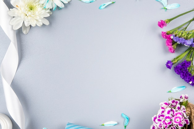 Draufsicht der rosa und lila statice blumen mit weißer chrysantheme und band auf weißem tisch mit kopienraum