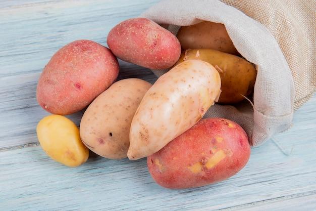 Draufsicht der rostroten neuen und roten kartoffeln, die aus sack auf holzoberfläche verschüttet werden