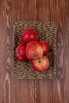 Draufsicht der roten äpfel im korbteller auf holztisch
