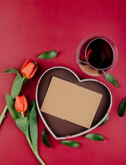 Draufsicht der roten farbe tulpenblumen mit herzförmiger geschenkbox mit einer offenen postkarte und einem glas rotwein auf rotem hintergrund