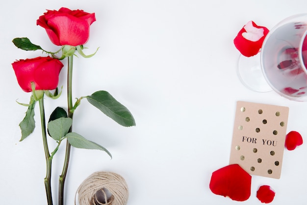 Draufsicht der roten farbrosen mit einer kleinen postkarte des glases des rotweins mit seil auf weißem hintergrund mit kopienraum