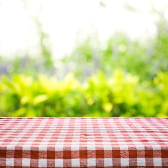 Draufsicht der roten karierten tischdeckenbeschaffenheit mit abstraktem grün vom gartenhintergrund.