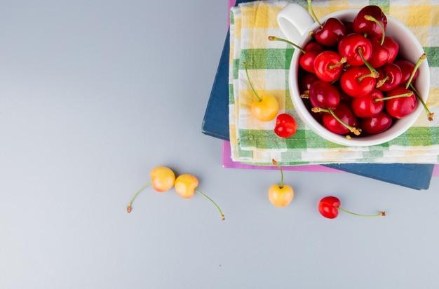 Draufsicht der roten kirschen in der tasse auf stoff und bücher mit gelben kirschen auf blauer oberfläche mit kopienraum